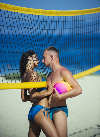 Sport activity and health. Sexy woman and muscular man with ball at net. Summer vacation and travel on holiday in Miami. Love and flirting of couple. Couple in love play volleyball on sunny beach.