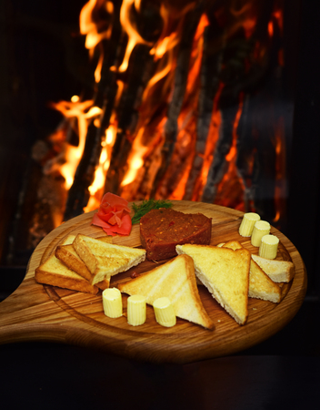 Tatar beefsteak served in shape of heart on round wooden board. Bread, toast and butter around beefsteak on board. Restaurant dish concept. Dish appetizing decorated with dill, fire on background.