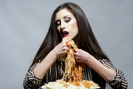 Sexy woman eat spaghetti with hands. Woman eat pasta dish with tomato ketchup. Hungry girl have italian food meal. Beauty model with makeup and long brunette hair have dinner. Food, diet and cuisine.