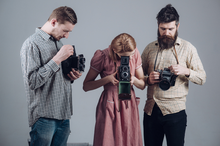 Vintage photography concept. Men in checkered clothes, retro style. Company of busy photographers with old cameras, filming, working. Men and woman on pensive faces on grey background.