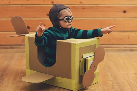 Dream, career, adventure, education. Air mail delivery, aircraft construction. Pilot travel, airdrome, imagination. Kid, pilot school, innovation. Little boy child play in cardboard plane, childhood.