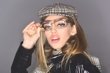 Woman on pensive face with make up wears checkered accessories and glasses for vision. Accessories concept. Girl wears kepi, scarf and glasses, grey background. Sexy lady in stylish outfit, close up.