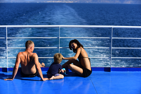 Mother and father with son in sea on yacht. Family travel with kid on mothers or fathers day. Love and trust as family values. Child with father and mother. Summer vacation of happy family