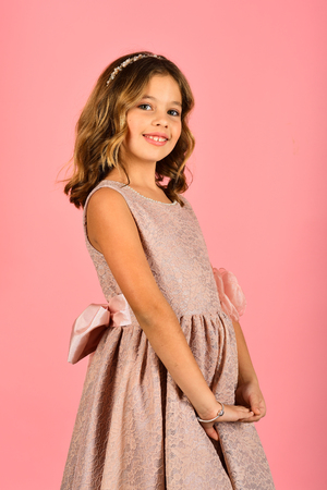 Fashion and beauty, little princess. Little girl in fashionable dress, prom. Child girl in stylish glamour dress, elegance. Fashion model on pink background, beauty. Look, hairdresser, makeup.