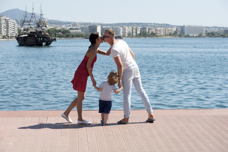 Summer vacation of happy family. Family travel with kid on mothers or fathers day. Love and trust as family values. Child with kissing father and mother. Mother and father with son at bay with ship. Standard-Bild