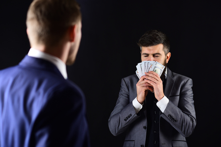 Man with beard on calm face sniffing money, smell of profit. Meeting of reputable businessmen, black background. Business payment concept. Businessmen, business partners counting profit.