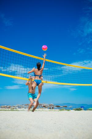 Sommerferien und Urlaubsreisen in Miami. Sommerferien des glücklichen gesunden Paares, das Volleyball am Strand zahlt
