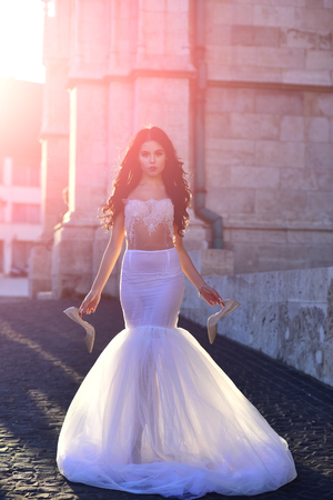 Beautiful bride walk on the street at stony building Stock Photo