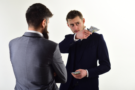 Businessmen, business partners counting profit. Meeting of reputable businessmen, white background. Man in suit on serious face counting money, pay to partner. Business payment concept.