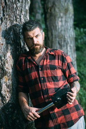 Brutal lumberjack holding small spade and leaning on old tree. Hipster with stylish beard wandering in wilderness. Young concentrated scientist working in nature, environment and ecology concept. Фото со стока