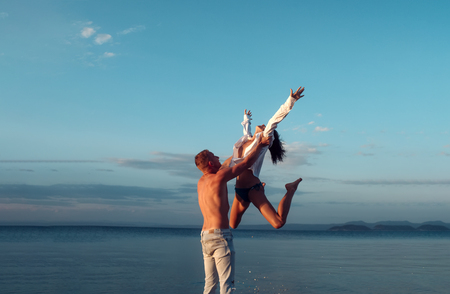 Love relations of naked couple at sea. Summer holidays and paradise travel vacation. Happy family and valentines day. Sexy woman and man jump. Couple in love with sexy body relax on beach Imagens
