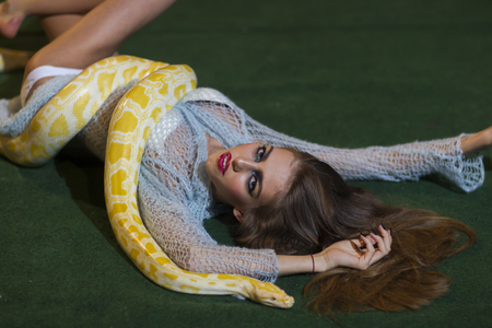 Snake crawl on woman with long hair. Sensual woman relax with albino python. Beauty model with makeup face and yellow serpent. Danger temptation and desire concept.