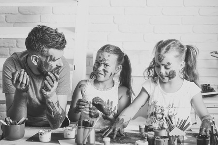 Dad and daughters drawing with colorful paints
