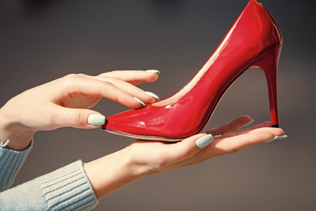 shoe red color leather on female hand on blurred background, fashion and beauty, shopping and presentation, cinderella Stock Photo