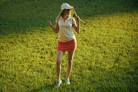 Girl athlete in sexy uniform, cap on green grass