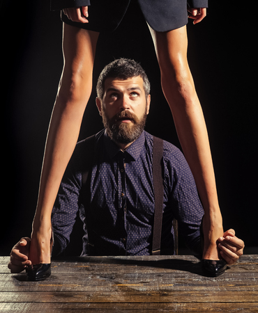 Businessman at table with female legs. Stockfoto