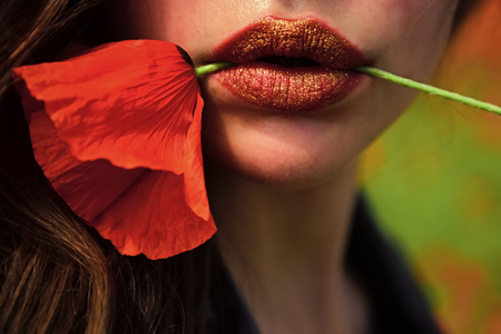 Beauty, summer, spring, poppy. Opium poppy, cosmetics, ecology, sexy lips. Drug and love intoxication, opium, fashion. Poppy, Remembrance day Anzac Day Woman with poppy flower in red lips makeup Stock Photo