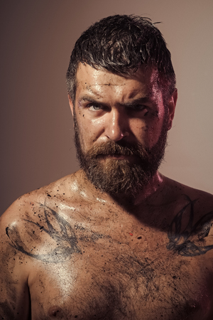 Bearded man with tattoo on chest skin Фото со стока