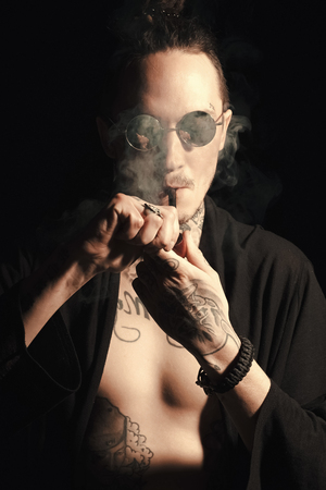 Guy smoker in sunglasses and open clothes showing tattooed torso