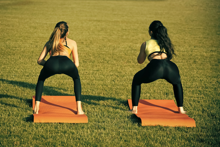 Health women do athletic exercises on green grass Stockfoto