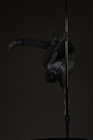 Young strong pole dance man on dark background. Guy with nude torso performing pole dancing moves on pole.
