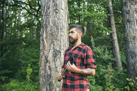 Bearded man with spade wandering in woods. Side view brutal lumberjack waiting on path. Nature, camping, leisure concept.