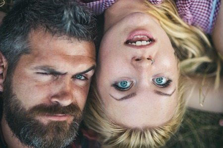 Romantic couple lying in park. Excited blond girl and brutal bearded man side by side on grass view from above. Sweethearts having fun in summer.