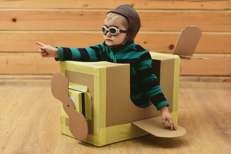 Air mail delivery, aircraft construction. Dream, career, adventure, education. Kid, pilot school, innovation. Little boy child play in cardboard plane, childhood. Pilot travel, airdrome, imagination.