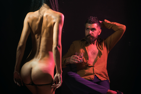 Call girl, striptease, massage. Man drink whiskey, naked woman, valentines day. Couple in love with sexy body, relax. Love, relations, couple in love, buttocks. Sex games, desire, orgasm, foreplay.