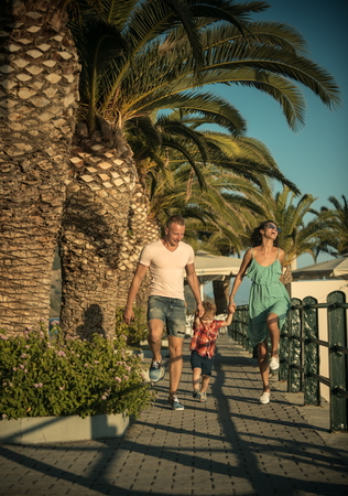 Summer vacation of happy family. Mother and father with son walk at beach palms. Child with father and mother. Family travel with kid on mothers or fathers day. Love and trust as family values.
