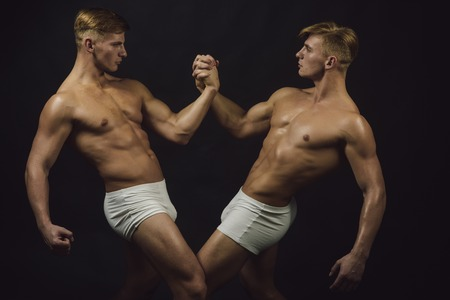 Friendship of men do gymnastic. friendship of twins men with muscular body in bodybuilder pose