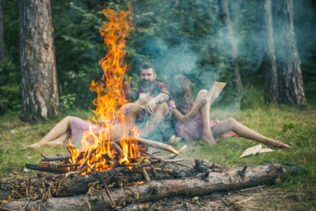 Bonfire flame with sparks and people on background. Fire burn in camp. Friends relax in smoke of campfire. Camping, hiking and travel. Summer vacation concept.