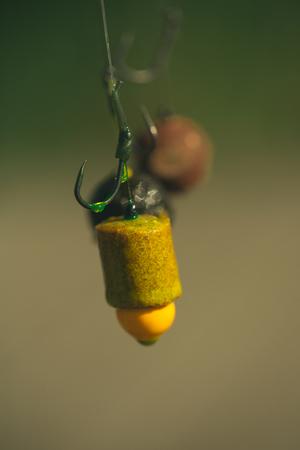 Hooks with fishing bait, chumming. Fishhooks on line on blurred background. Fishing, angling, catching fish, chum.