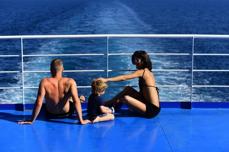 Family travel with kid on mothers or fathers day. Mother and father with son in sea on yacht. Love and trust as family values. Child with father and mother. Summer vacation of happy family