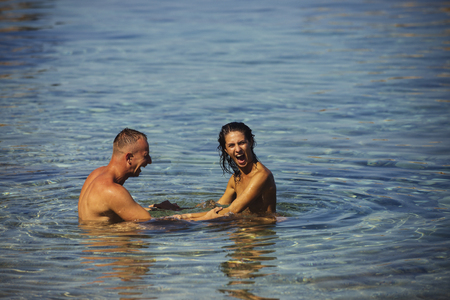 Love relations of naked couple in sea water. Sexy woman and man swim. Family and valentines day concept. Couple in love with sexy body relax on beach. Summer holidays and travel on vacation Standard-Bild