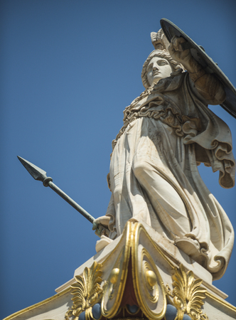 Statue, sculpture of Greek warrior in helmet with spear and shield. White sculpture ancient greek god of war with gilding. Statue of man in armor with blue sky on background.