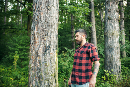 Side view brutal man standing next to tree. Bearded hipster wandering in forest. Camping, nature concept.