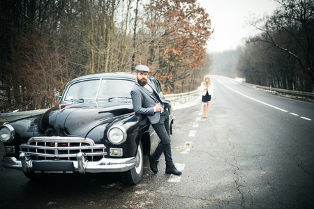 Retro collection car and auto repair by mechanic driver. Couple in love on romantic date. Travel and business trip or hitch hiking. Bearded man and sexy woman in fur coat. Escort of girl by security