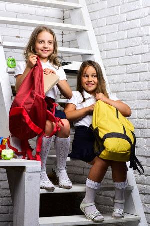 girls put book and notebook into backpack.