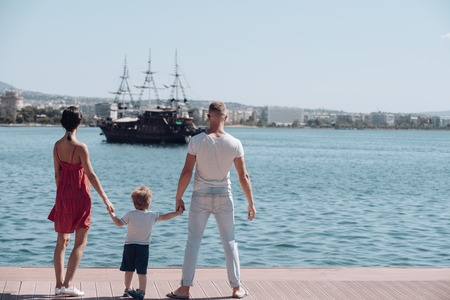 Family travel with kid on mothers or fathers day. Child with father and mother. Love and trust as family values. Summer vacation of happy family. Mother and father with son look at bay with ship. Imagens