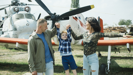 Happy family spend time together, on excursion, helicopter or plane on background, sunny day. Mother and father and their child walking in aviation museum outdoors. Development and upbringing concept. Banco de Imagens
