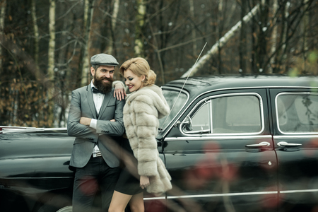 Travel and business trip or hitch hiking. Escort of girl by security. Couple in love on romantic date. Retro collection car and auto repair by mechanic driver. Bearded man and sexy woman in fur coat Stock fotó
