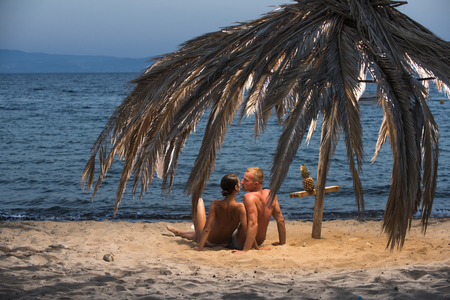 Family and valentines day. Summer holidays and paradise travel vacation. Love relations of naked couple on sand. Sexy woman and man with pineapple. Couple in love with sexy body relax on beach