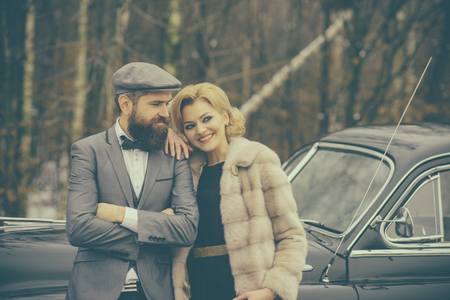 Couple in love on romantic date. Escort of girl by security. Retro collection car and auto repair by mechanic driver. Bearded man and sexy woman in fur coat. Travel and business trip or hitch hiking