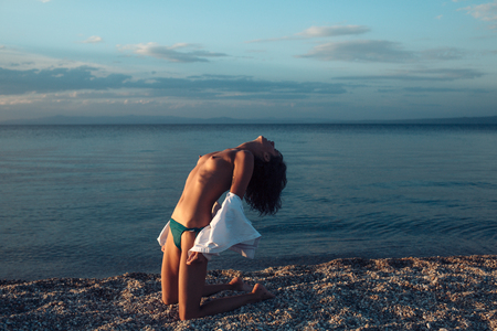Summer holidays and paradise travel vacation. Sexy woman sit on sand with naked chest in sunset. naked woman at sea sunrise. sensual girl with sexy body relax on beach. nature and environment. 스톡 콘텐츠 - 101171990