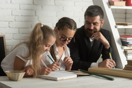 father and daughters writing white home schooling. Father helps children to study at home