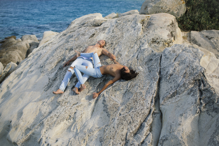 Love relations of naked couple on sea. Sexy woman and man in jeans on stone. Summer holidays and paradise travel vacation. Couple in love with sexy body relax on beach. Family and valentines day Foto de archivo - 101172678