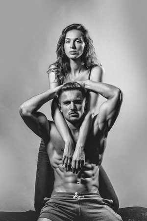 Prelude - couple in love. Man with muscular torso and athletic body in studio on grey background. Stock Photo