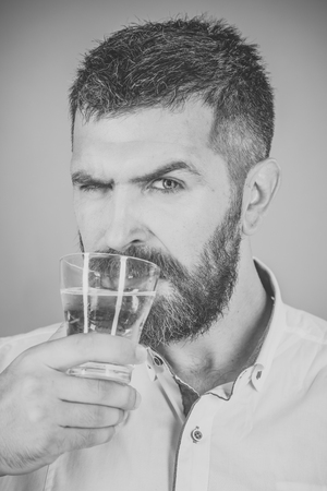 man with beard on serious face drink water from glass