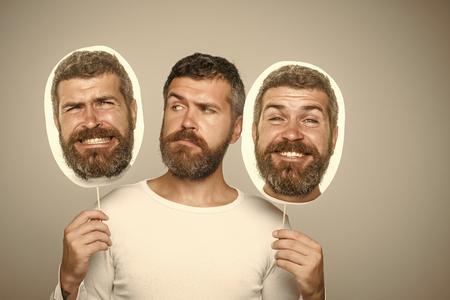 Hipster with serious, happy and scary face hold portrait nameplate. Stockfoto